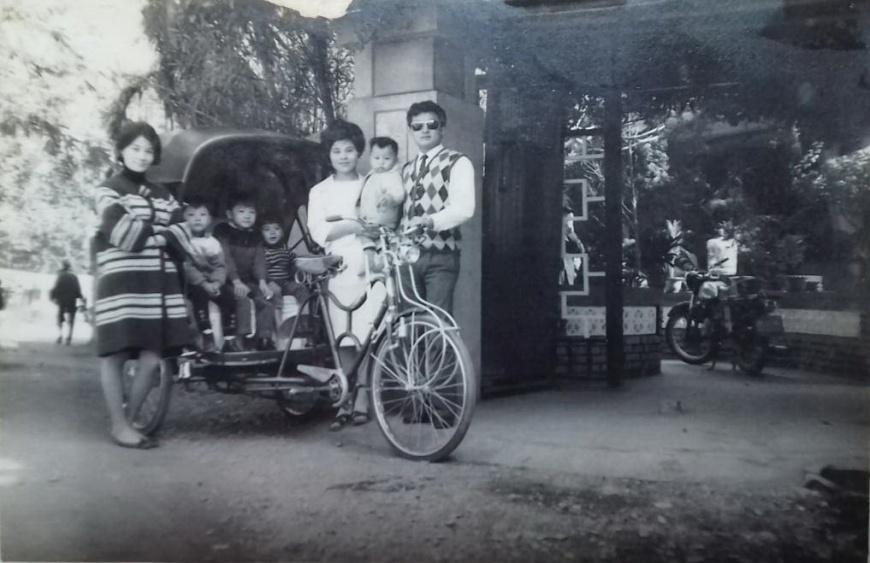 六歲以前,作者家裡頭也曾經擁有過一輪黑色頂蓬的三輪車,站在畫面右邊的正是作者的爸、媽,襁褓中的作者當時還不足兩歲。(照片攝於1968年)