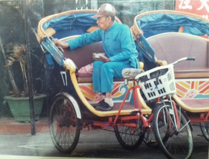 在旗津踩了幾十年三輪車的老阿伯,津津有味地品嚐老伴為他準備的午餐便當。黃映溓攝於1987年,時至今日,旗津景況依舊。