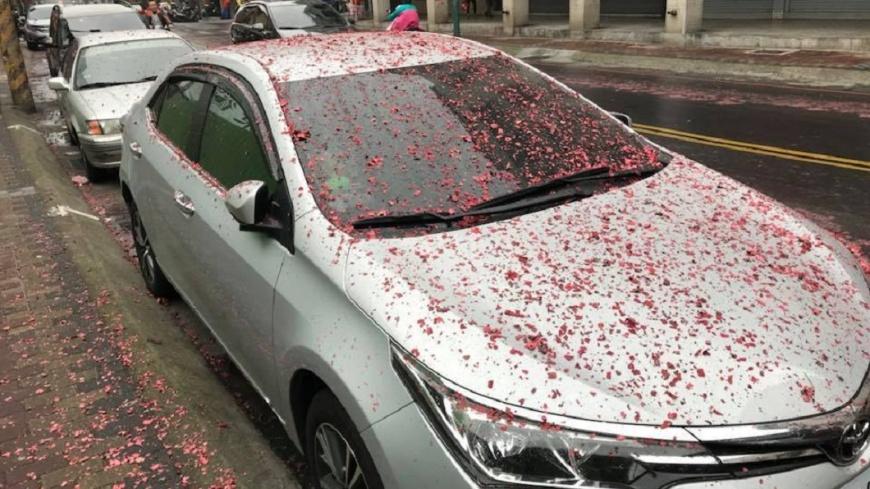 有廟會繞境沿路施放鞭炮,民眾除了抱怨噪音之外,碎屑更是造成沿路髒亂,還有人的車子被波及。(圖/翻攝自爆料公社) 8+9祝福?鞭炮沿路炸1小時 轎車蓋滿紅色碎屑