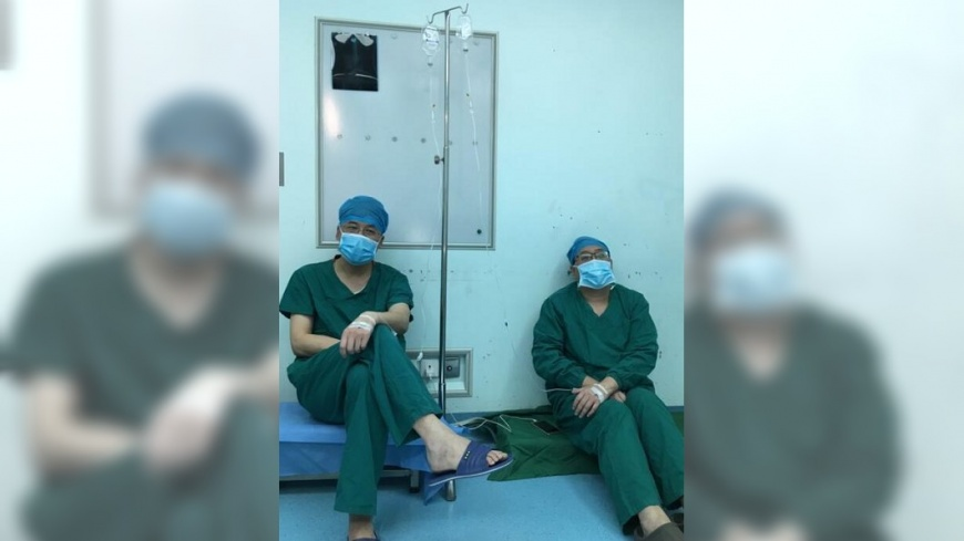 2名醫師連續開刀10小時候累癱,趁著空檔打點滴補體力,網友看了超心疼。(圖/翻攝自華商報) 2醫師連開刀10小時累翻 趁空檔「靠牆打點滴」