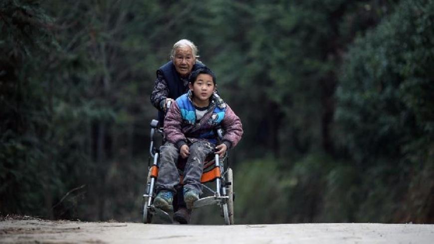 大陸一名76歲的史玉英老奶奶,每天來回24公里推著輪椅送腦麻的孫子去上下學。(圖/翻攝自漢豐網) 每日走24公里 76歲嬤送腦麻孫上下學