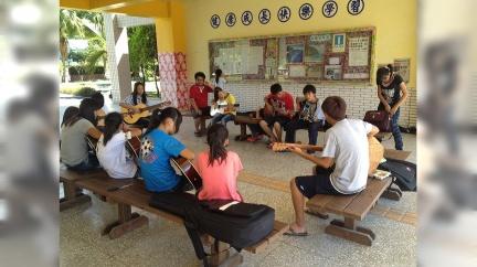 謝明賢(紅衣者)在才藝班陪學生練習吉他。/劉佑祖提供