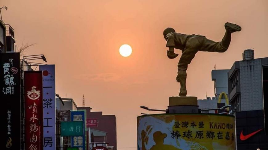 攝影師巧妙融合雕像,形成1幅「嘉農投好球」的美照。圖/攝影師洪年宏授權提供