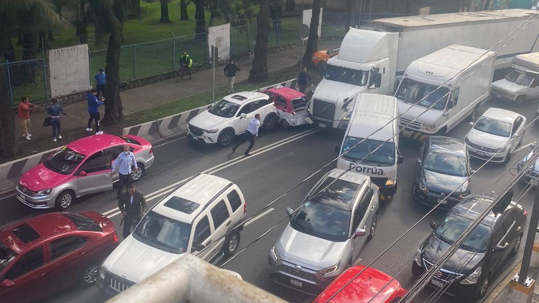聯結車在馬路上上演硬鑽車縫的瘋狂戲碼。(圖片來源/ 擷取自Yamile Rodríguez Twitter) 把聯結車當坦克開?  跑路遇塞車「直直撞」到底