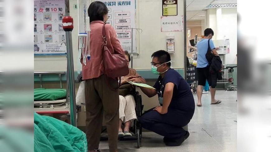 急診室中一位醫師蹲著身子,耐心地聽一位鄉音很重的老奶奶講述自己的狀況。圖片來源/爆料公社粉絲團 老奶奶鄉音重!急診暖醫蹲10分鐘 耐心聆聽安撫