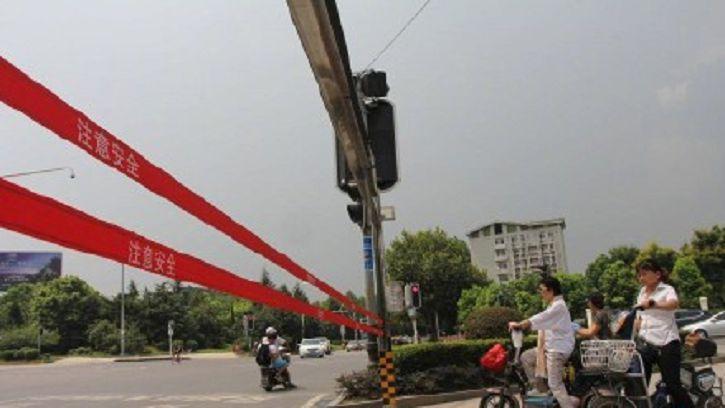 武漢市出現這款「自動拉繩系統」,據說讓當地民眾闖紅燈的行徑大大降低。(圖/翻攝自微博) 防闖紅燈新神器!陸「自動拉繩」攔阻行人