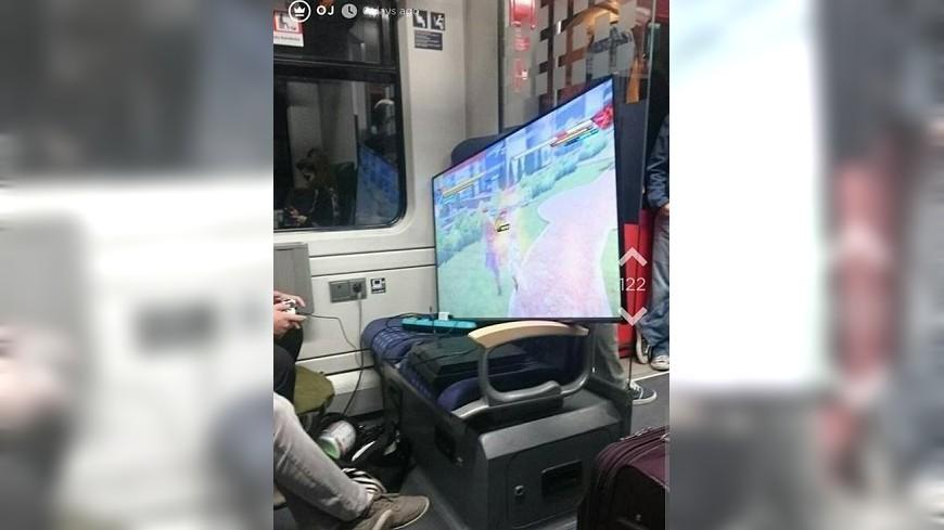 德國有男子搭火車時,直接搬來一台50吋大電視玩起PS4遊戲,其他乘客都驚呆了。(圖/翻攝自推特)