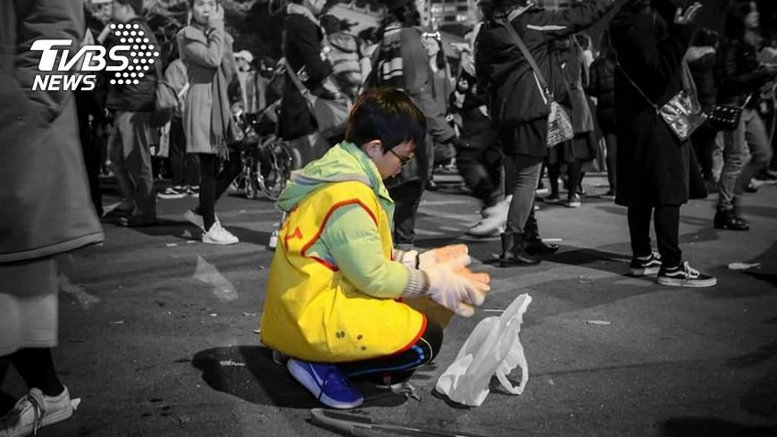 影像工作者捕捉到志工小男童蹲在地上撿垃圾,與來往的人潮形成強烈對比,讓他內心頗為震撼。(圖/網友陳家威授權提供) 震撼!跨年夜人潮散去 小男童當志工默默撿垃圾