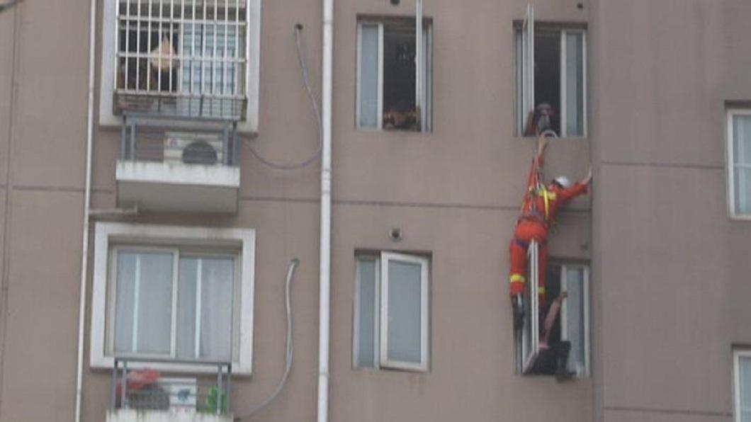 南京一名婦人欲從8樓一躍而下,消防人員垂降神來一腳,把婦人踹回屋內。(圖/翻攝自揚子晚報) 母帶3歲童欲跳8樓 消防員垂降「踹」她一腳回屋內