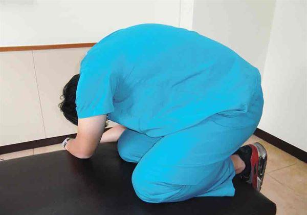 【下背拉筋運動】:跪坐姿,彎腰趴下偏向1側。圖片來源/活力得中山脊椎外科醫院