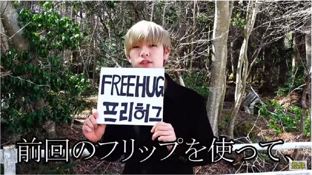 網紅舉了一個「FREEHUG(免費擁抱)」的牌子。(圖/翻攝自YouTube)