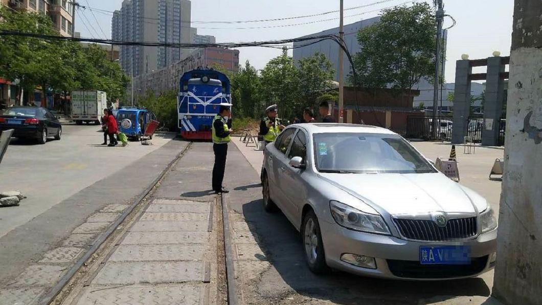 一名車主將車停在社區門口,卻逼停一輛經過的火車。圖/翻攝自華商網