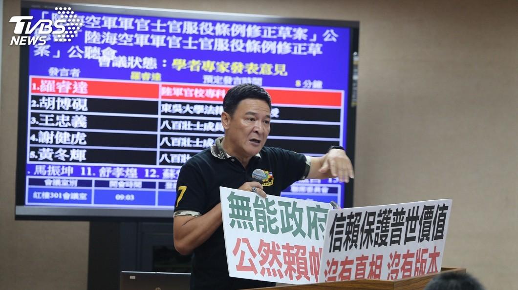 八百壯士羅睿達在公聽會舉標語抗議,大罵政府無能也無信。(圖/中央社,TVBS) 軍改公聽會火爆 八百壯士怒嗆:國防部退輔會官員是走狗