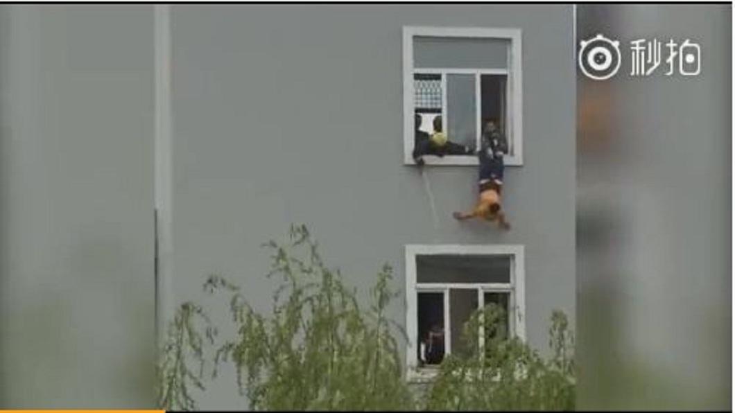 哈爾濱一名男子企圖跳樓輕生,消防員緊急抓住他的褲子試圖援救。(圖/翻攝自微博) 男尋短不願被救 脫掉褲子5樓墜下亡
