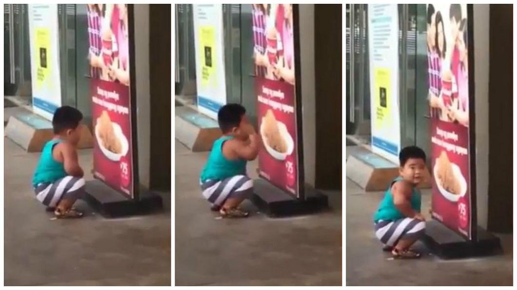 菲律賓一名小胖弟超想吃炸雞,竟然就蹲在海報前隔空抓來吃。(圖/翻攝自臉書) 小胖弟想吃炸雞 對著海報隔空「抓」來吃