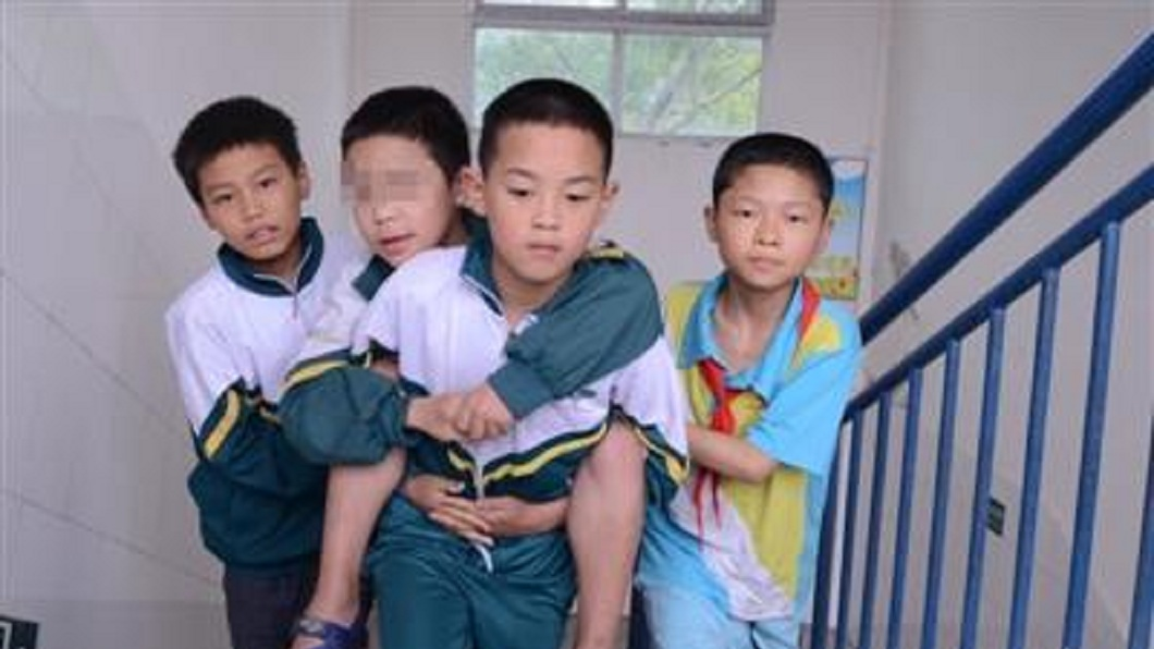 古小鑫(左二)因罹患腦麻無法行走,同學們自發性地揹他上下樓。(圖/翻攝自網易新聞) 超暖!小五童腦麻無法走 同學每天背還在旁護衛
