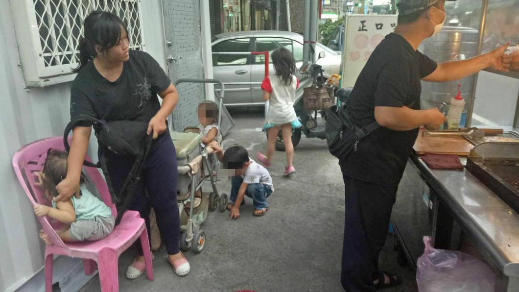 柯爸爸在攤位前忙著煎蔥油餅,妻子則在一旁照顧4個孩子。(圖/「光線」臉書粉絲團授權提供)