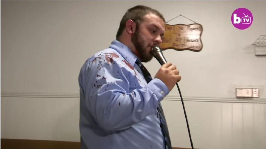 牧師被蛇咬了耳朵一口後,血跡染紅了他的襯衫。(圖/翻攝自YouTube)
