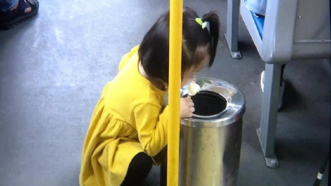 大陸網站流傳一張照片,一名小女孩在公車上蹲在垃圾桶旁吃冰棒。(圖/翻攝自陸網) 怕弄髒公車地板…2歲女孩蹲在垃圾桶旁吃冰棒