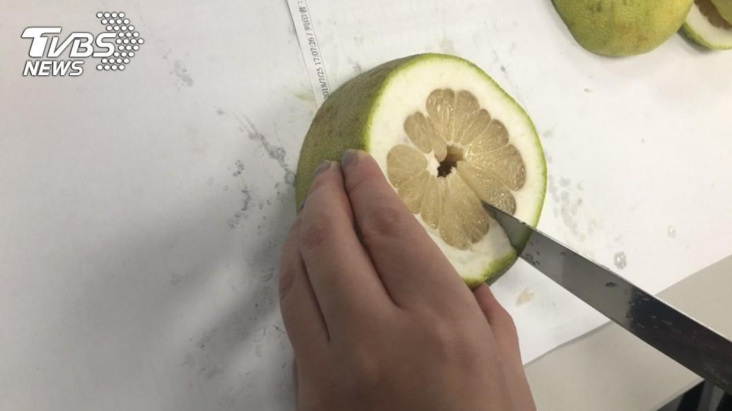 剖半的柚子,各在側邊切上一刀
