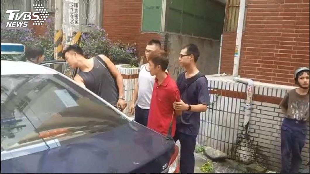 現場便衣刑警將砸雞蛋的男子上警車帶回偵訊。(圖/TVBS)