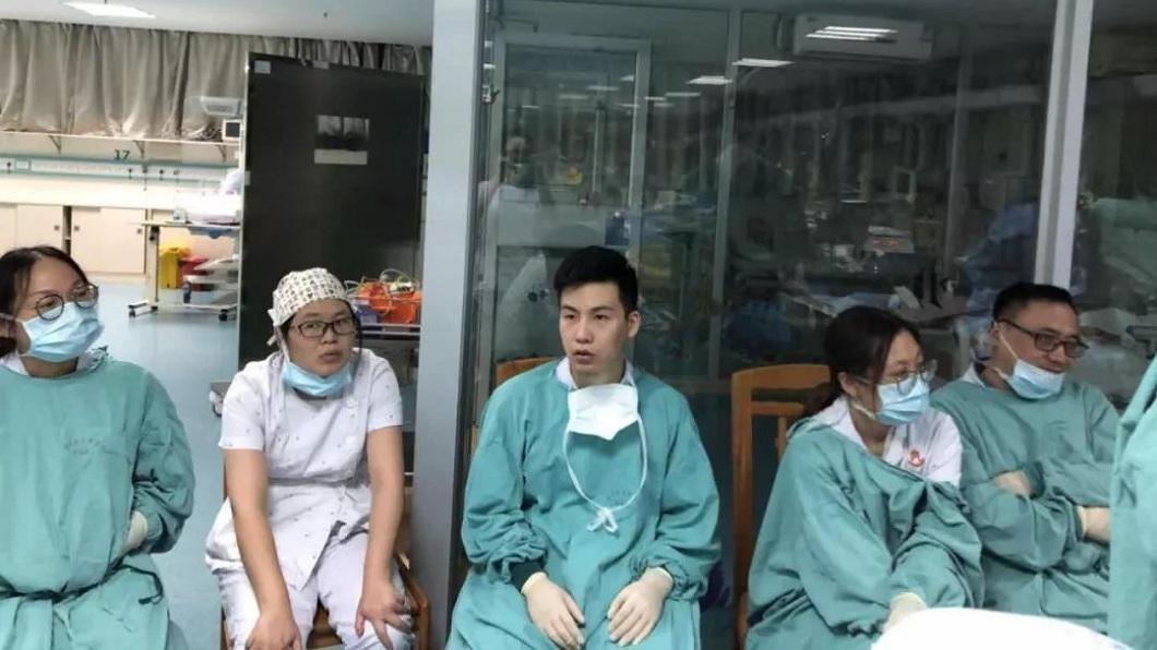 30多名醫護人員5小時內輪流幫小雨進行3萬次胸外心臟按壓,最後累倒在一旁休息。(圖/翻攝自微博)