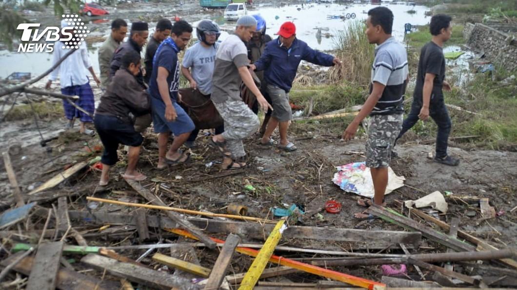 巴路市居民正扛著因海嘯而身亡的人。(圖/達志影像美聯社)