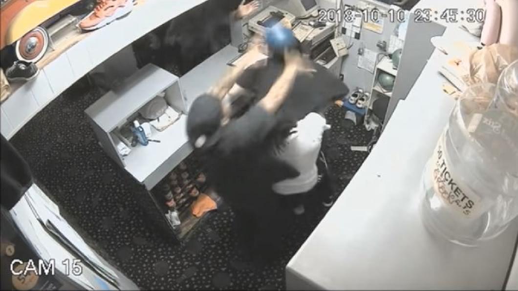 黑衣男更拿起保齡球朝店員的頭部砸過去。(圖/翻攝自YouTube)