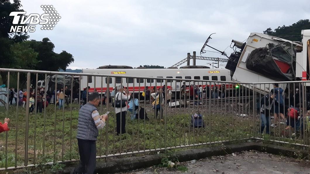 倖存乘客試圖在傾覆的車廂附近找尋失物。圖/TVBS