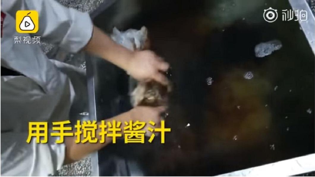 工作人員沒帶任何的手套或其他防護措施,直接用手抓肉去攪拌醬汁。(圖/翻攝自梨視頻)