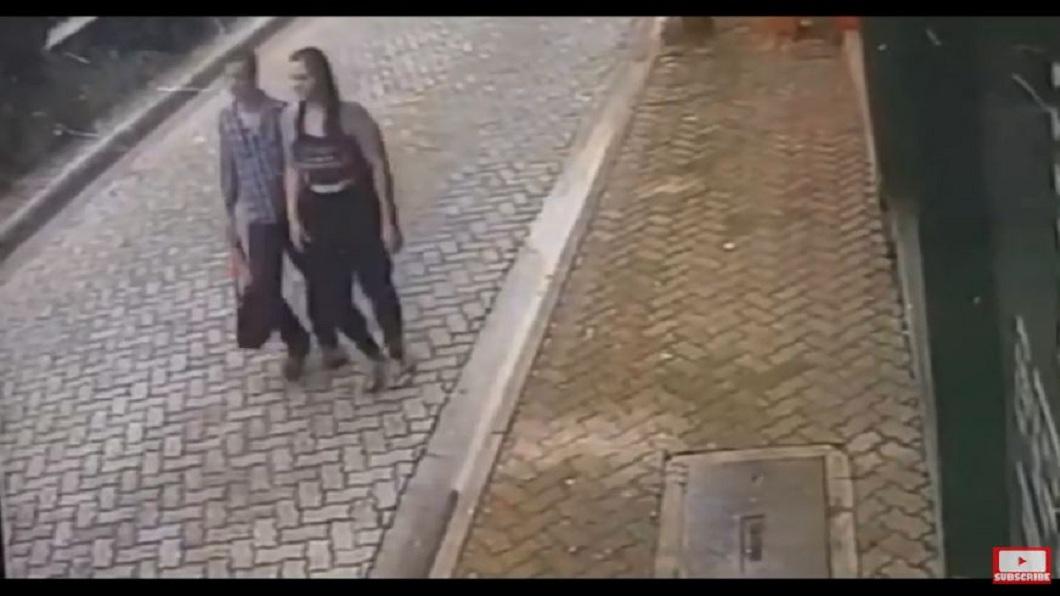國外一對情侶走在路上,不知道死神差點找上他們。(圖/翻攝自YouTube) 真男人!轎車天外飛來 他捨身護女友躲死劫