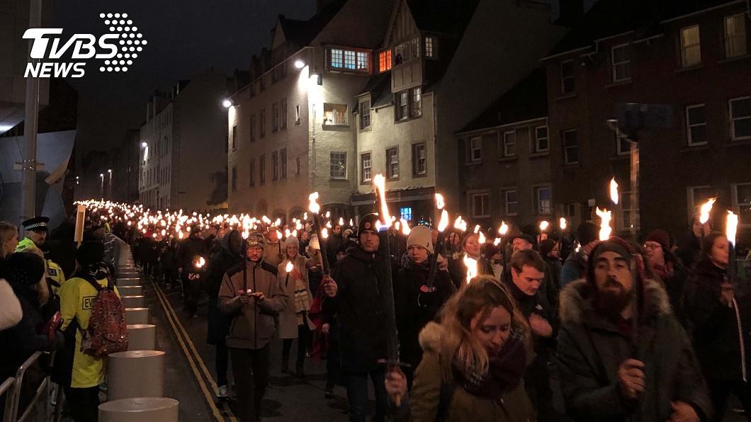 蘇格蘭首府愛丁堡的跨年活動30日晚上起跑,8000人手持火炬繞行愛丁堡街頭。(圖/中央社)