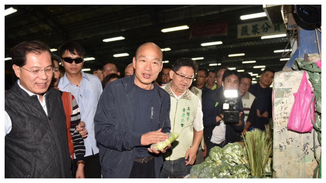 高雄市長走馬上任第一天,韓國瑜(左三)夜宿高雄十全果菜市場,緊跟在旁、邊聽邊做筆記的人,是高雄新任農業局長吳芳銘(左一)。距離他們宣布就任新職的時間還不到24小時,他們隨時已在掌握攤商心聲、農產運銷「價」與「量」的供需。   圖/中央社