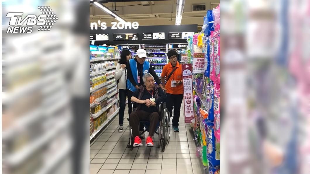 丁陳阿嬤在志工們協助下,坐輪椅到賣場買年貨。圖/弘道老人福利基金會提供