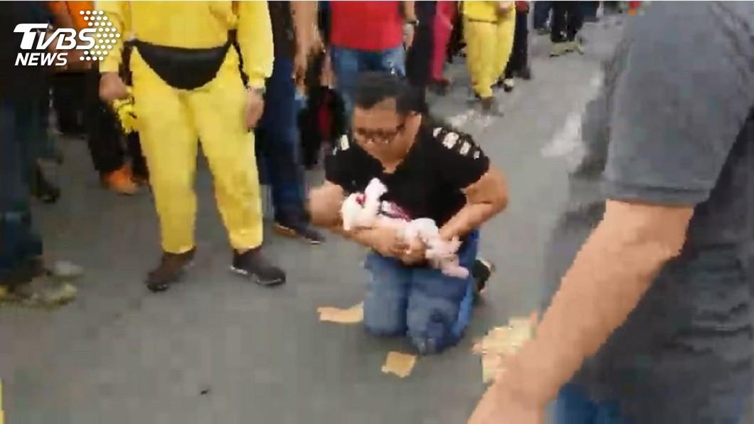 屏東里港一名媽媽得知白沙屯媽祖抵達,抱著孩子跪在馬路上向媽祖祈福。(圖/TVBS,網友鄭有承授權提供)