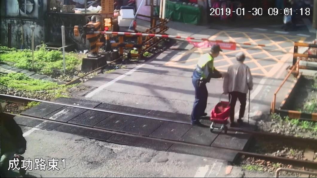 圖/中央社 老婦拖菜籃車過平交道 遮斷器突降下暖警伸援