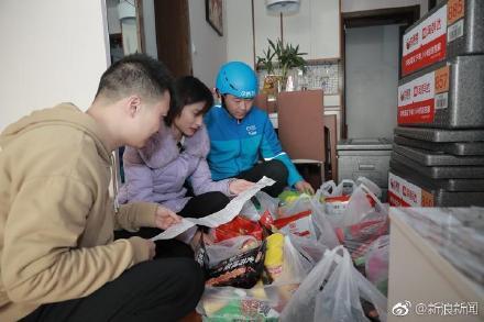 陸姓男子和女友與送貨員核對8箱零食。圖/翻攝自微博