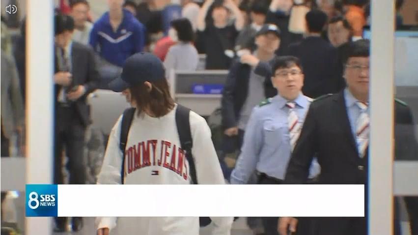 鄭俊英(左,白衣者)12日晚間返回韓國,將接受警方調查。圖/翻攝自SBS 8點新聞