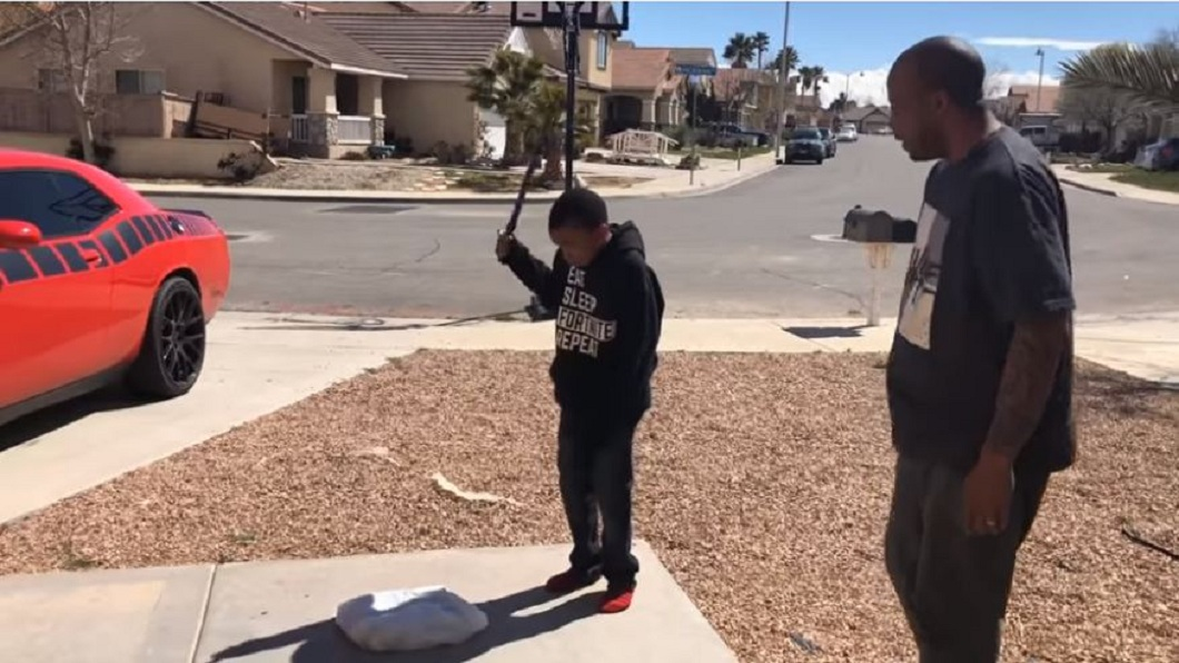 美國一名人父不滿兒子成績退步,要孩子拿著鐵棍把PS4主機敲毀。(圖/翻攝自YouTube) 小學兒成績退步 虎父怒逼他親手砸爛PS4再開車輾爆