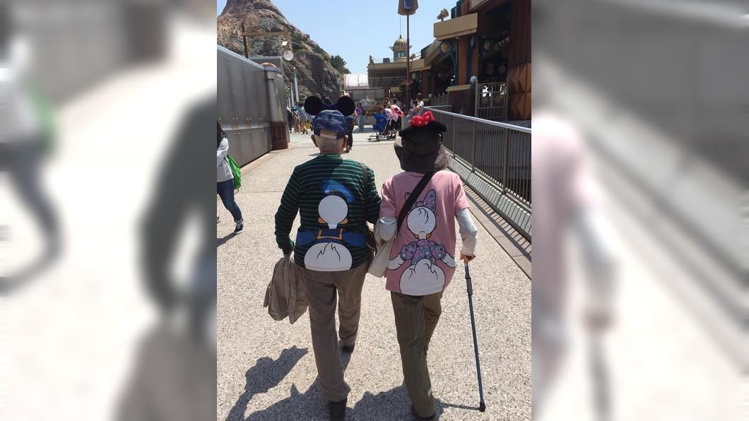 有網友分享一對老夫妻在迪士尼樂園牽手的背影照,大家看了都超羨慕。(圖/翻攝自爆笑公社)