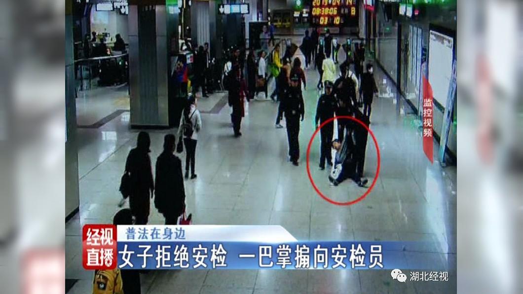 圖/翻攝自湖北經視 過安檢會中毒?藍衣女鬧地鐵站甩人巴掌被警拖走