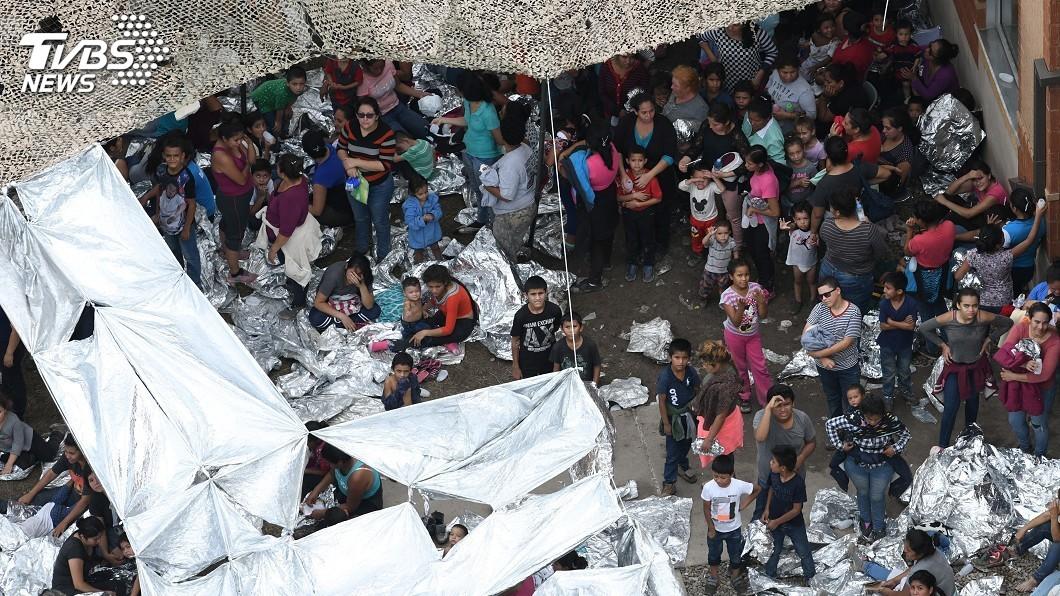 圖/達志影像路透社 男女老幼席地睡 一張空拍照看出移民慘況