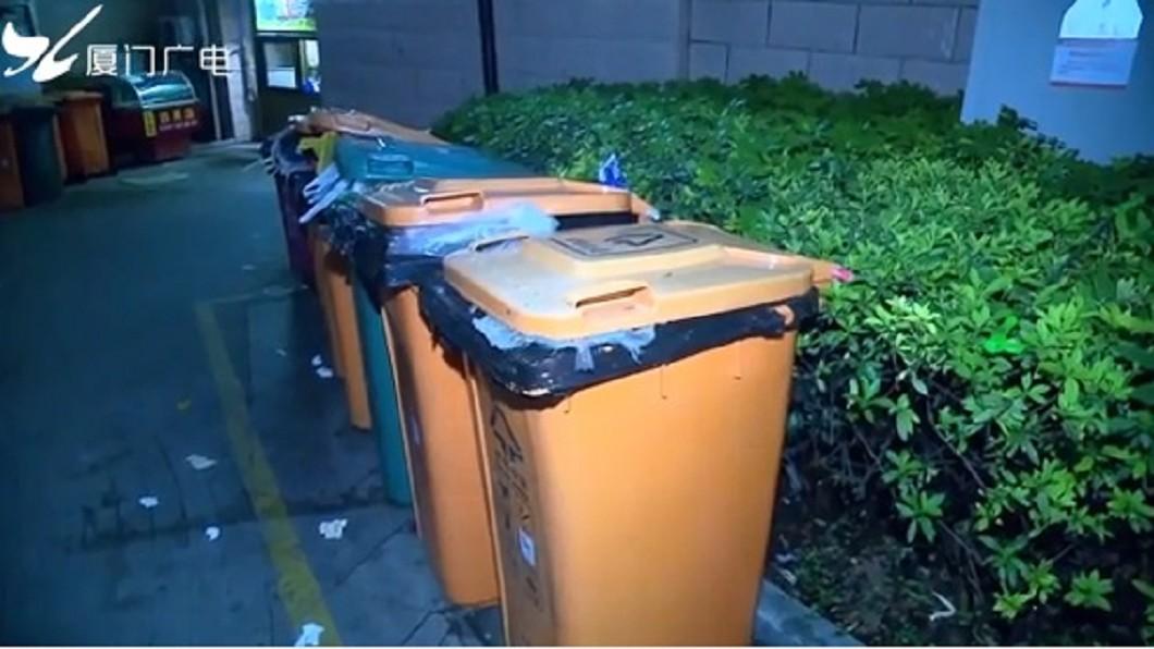 女清潔隊員葉秀華在垃圾桶內,發現活生生的男嬰。圖/翻攝自廈門廣電 女謊稱「狗死了」隨便丟 清潔員翻開驚見一男嬰腿在動