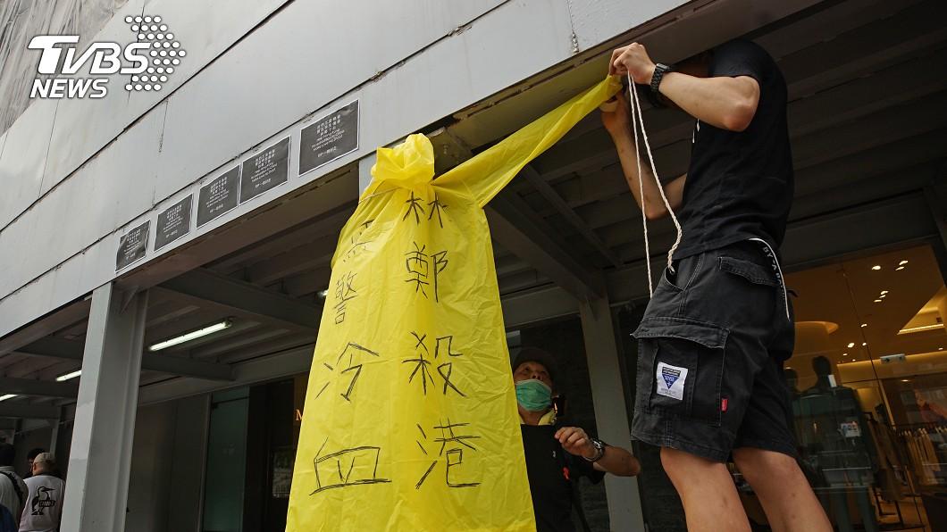 香港反送中支持者墜樓 民眾掛標語表訴求(圖/中央社) 抗議逃犯條例墜樓亡 港民一人一花悼念黃衣男