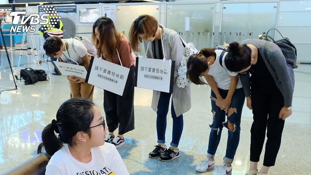 空服員身上披掛「請不要責怪地勤」的標語,在長榮櫃檯前鞠躬致歉,地勤僅點頭示意 圖/TVBS 空姐酸地勤:你這張臉能考上空服員嗎 網友:內心醜陋