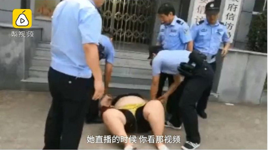 警方接獲報案前往現場逮人,沒想到女子卻耍賴躺在地上。(圖/翻攝自梨視頻)