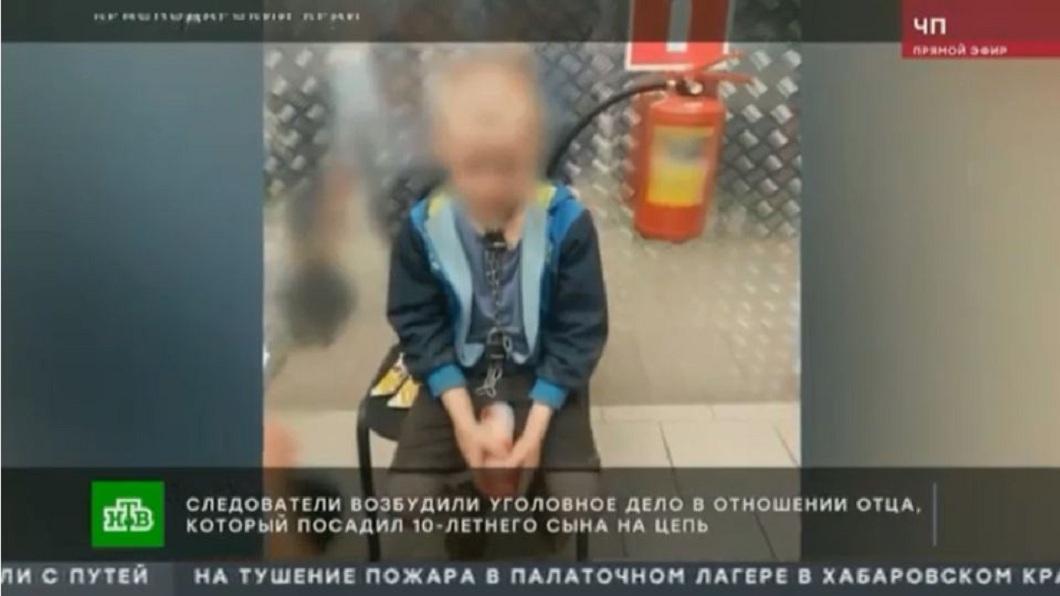 俄羅斯一名10歲男童,脖子上綁著鐵鍊還有2道鎖出現在超市,引發當地的關注。(圖/翻攝自YouTube) 10歲男童被鐵鍊鎖喉關地窖 冷血狠父:他自己綁的
