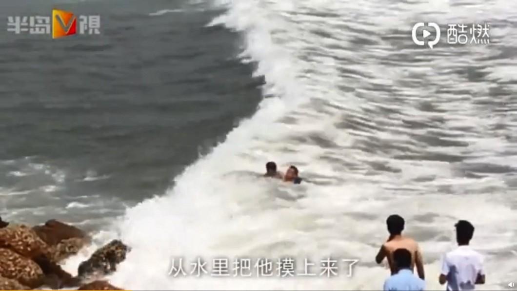 巨浪將岸邊的人捲入水中,情況相當危急。圖/翻攝青島發布微博 勇!巨浪捲4人入海 他流著血「1個1個救上岸」