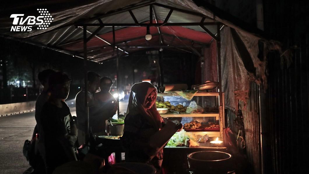 圖/達志影像美聯社 印尼大停電 民眾摸黑購物、捷運關乘客