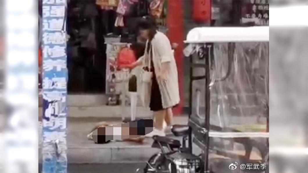 女子當街行兇之後,站在一旁不停甩手,想要把血甩掉。圖/翻攝軍武季微博 天氣熱想吃冰 男友回「這麼胖還吃」…被她拿剪刀捅死